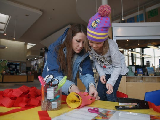 Briana Jensen, left, helps her daughter Emily Jensen craft a Chinese paper lantern during a Chinese New Year celebration Saturday at the Farmington Museum at Gateway Park.