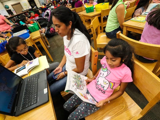 Celestina Garcia (left) and her sister rosa Garcia(right) read as their mother, Rosa Caniz, sits with them. reads during the Reading Blast event, Saturday, Jan. 21, at Orange River Elementary. This is an example of what one of Lee's schools is doing to bring parents on campus in a laid-back, reading-focused event.  About 100 students and parents go into the library, select books to check out and provide opportunity for the kids to read to their parents in English.