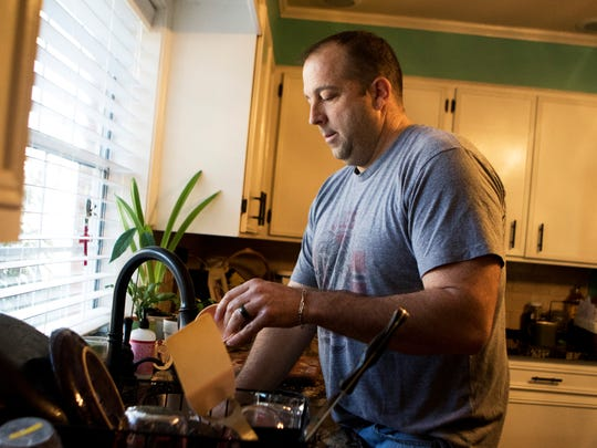 After making breakfast for his family at home in Monroe, Mark Phelps washes the dishes while his wife Melissa Phelps (not pictured) wipes off the counters on Saturday, January 28, 2017.
