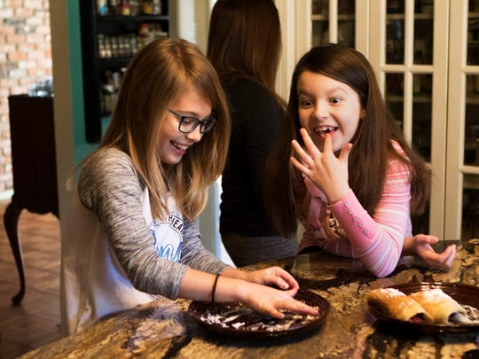 Nina Phelps, 8, right, makes a face as she and her friend Ellen Brockman, 8, lick the powdered sugar off a plate after making crepes for breakfast at home in Monroe on Saturday, January 28, 2017.