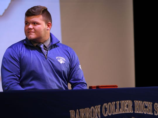 "Barron Collier football player Richard ""Ricky"" Gibson listens to Cougars head coach Mark Jackson speak prior to signing his letter of intent to play for the Indiana State football program during a signing day ceremony at Barron Collier High School on Wednesday, Feb. 1, 2017."