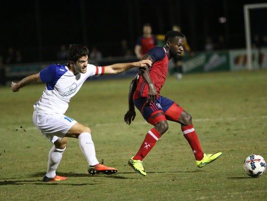 Albert Ruiz, left, and David Accam fight for possession