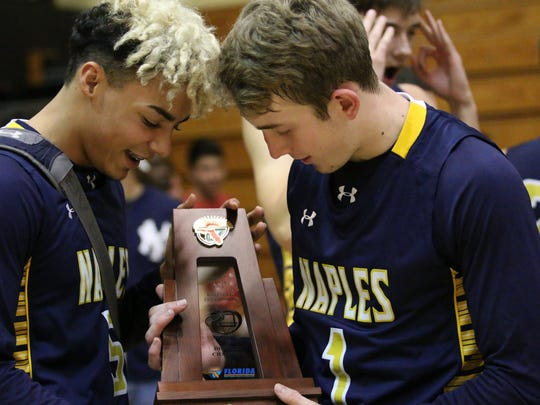 Darius Bradley, left, and Joseph Sushil hold the 7A-12 district championship trophy after defeating Golden Gate on Friday, Feb. 10, 2017. The Golden Eagles will host Fort Myers after beating the Titans, 86-84.