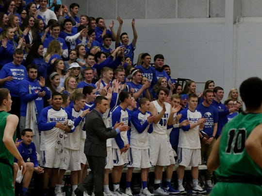 The student sections at Oshkosh West and Oshkosh North light up during the intercity rivalry games.