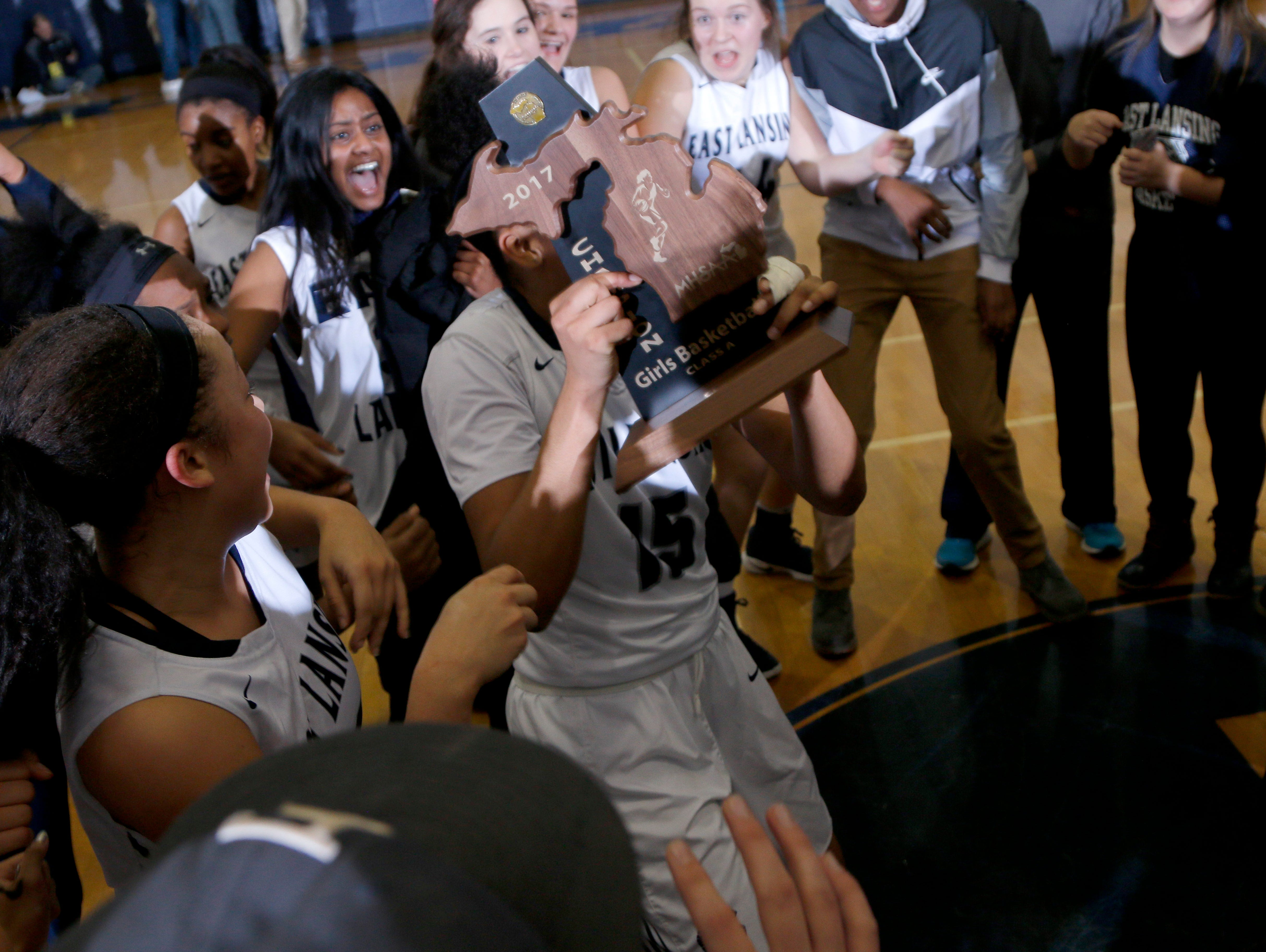 Players and fans celebrate East Lansing district final win over DeWitt Friday, March 3, 2017, in East Lansing, Mich. East Lansing won 48-47.