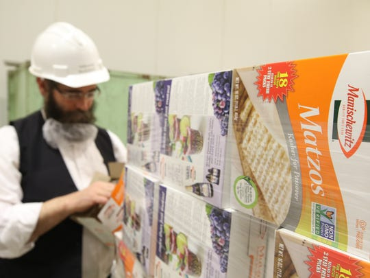 A pallet of matzos ready for shipping as Rabbi Aron Hayum, the plant manager at Manischewitz, opens a box.