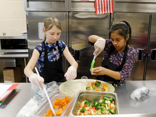 Zita Davis, left, and Karla Vasquez get samples of their culinary creations ready to be judge for the John Pittard Elementary Junior Chef Academy competition.