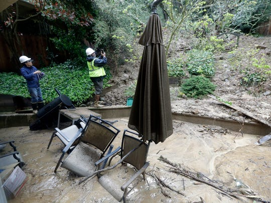 Workers survey a backyard damaged by a mudslide Friday in Oakland.