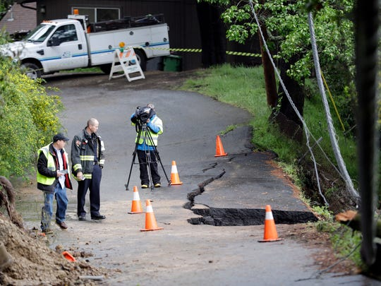 Emergency personnel and news crews survey a damaged road in the aftermath of a mudslide Friday in Oakland.
