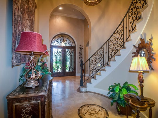 The grand entrance features marble floors and a beautiful staircase.