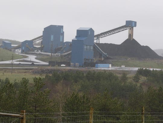 A large mountain of coal waits to be loaded onto trucks