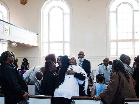 Hanifah Hightower, a ritual leader, hugs members of