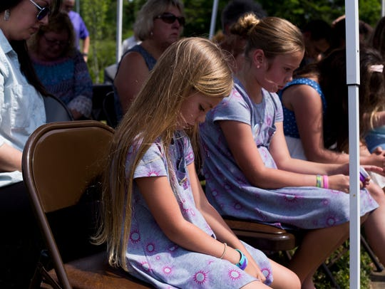 Guests lean their heads in prayer during the 8th annual