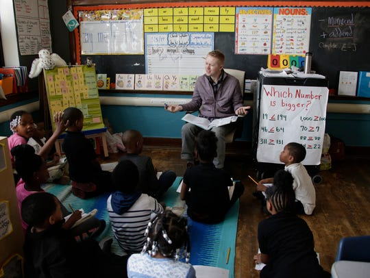 Second grade teacher Sean Deiters works with his students