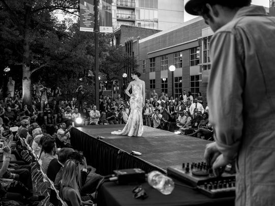 A model walks down a runway in the Iowa City pedestrian mall during the first Flyover Fashion Festival in May 2016.