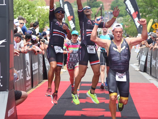 Triathletes cross the finish line of the 2017 Ironman 70.3 St. George race.