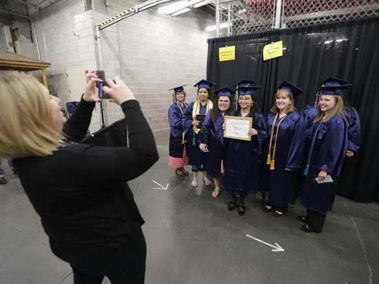 Maria Ortega, center, has her photo taken with fellow graduates Friday before the Northeast Wisconsin Technical College graduation ceremony at the Resch Center in Ashwaubenon.