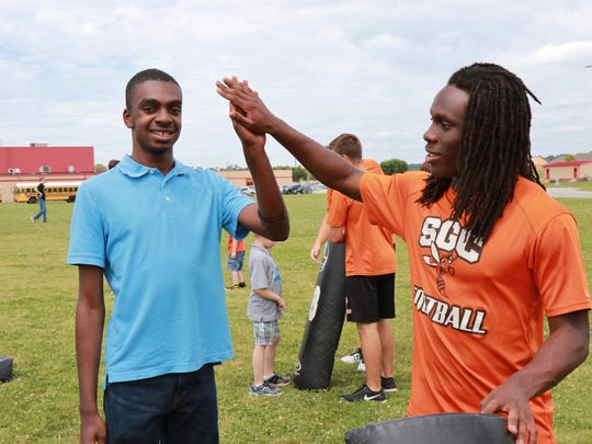 South Gibson running back Dre McAlister high-fives Johnaston Vaughn at the South Gibson All-Star Football Camp on Tuesday.