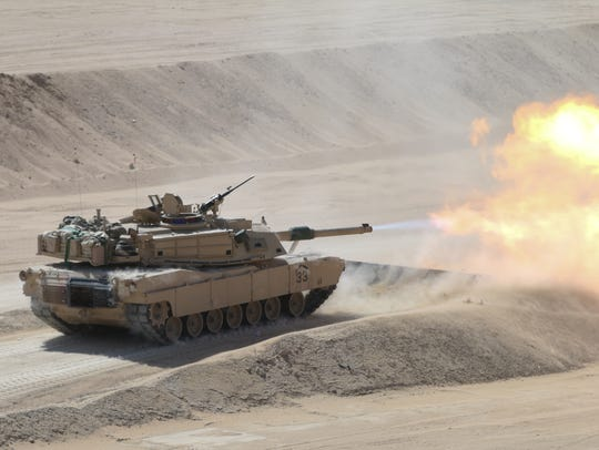 A tank with 3rd Brigade fires rounds down range at