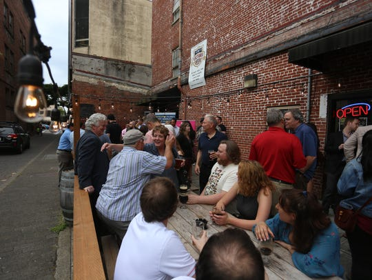 People sit outside the Victory Club bar in downtown