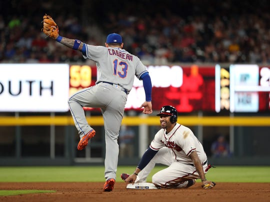 Atlanta Braves left fielder Matt Kemp (27, right) reacts after getting tagged out at second base on a stolen base attempt by New York Mets shortstop Asdrubal Cabrera (13) in the eighth inning at SunTrust Park on Friday, June 9, 2017.