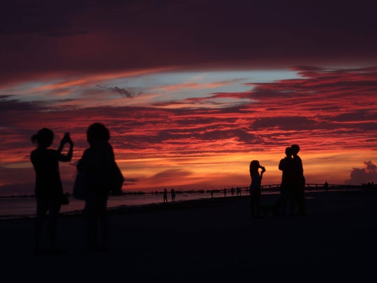 Visitors to Fort Myers Beach pier enjoy a  stunning sunset after an evening thunderstorm  on Tuesday.