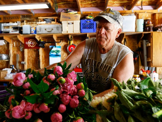 Grower Ed Smola drops off a load of peony stems on