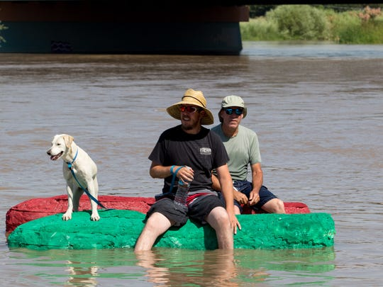 Two rafters and their loyal dog begin the float down the river during the Raft the Rio event held on June 17, 2017.