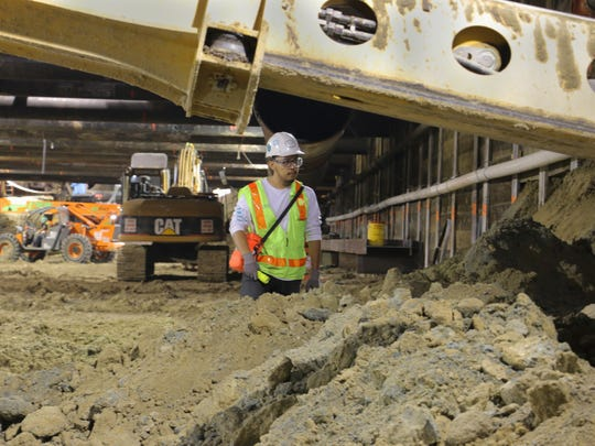 Paleontological monitor Francisco Palacios keeps watch as excavators dig up the earth four stories below surface level. Palacios' job is to look out for evidence of fossil remains while construction crews build the new Metro subway station.