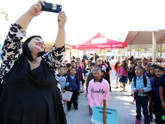 Lisa Gonzales-Solomon, principal of Madison Elementary School, snaps a selfie with students before class begins on Monday morning April 10, 2017.