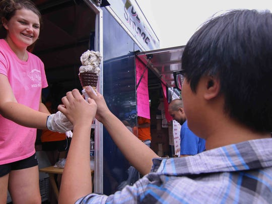Katie Leary of the IceCream Shoppe serves a double scoop of ice cream to Zekedela Cruz of Newark, during the 2015 New Castle County Ice Cream Festival at Rockwood Park.