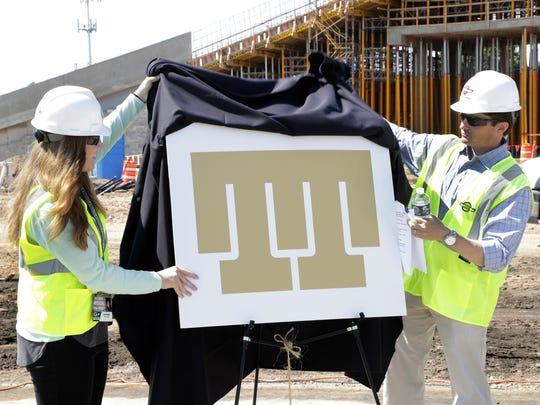 Green Bay Packers Vice President Ed Policy, right, and public affairs staff member Katie Hermsen unveil the new Titletown District logo Tuesday, June 27, 2017 in Ashwaubenon, Wis.