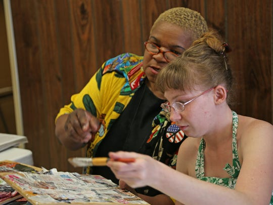 Georjeanna Feltha, left, helps a member of the Beloved  Community at an intergenerational art workshop
