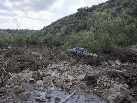 A car at the Chimney Ranch Mobile Home Park sits in a creek on July 20, 2017, after a flood in Mayer, Arizona, swept it away.