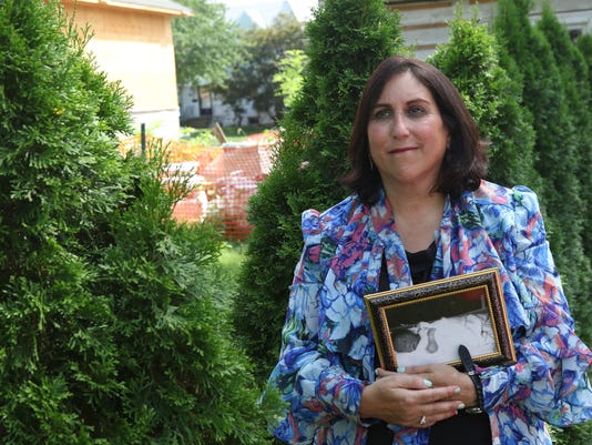 Reva Judas stands in her backyard by by trees that symbolize family while holding a photo of her son, born 30 years ago but who only lived for 12 hours. Today, she has grown children and after experiencing six miscarraiges now consels families who have lost children before, after or during childbirth.