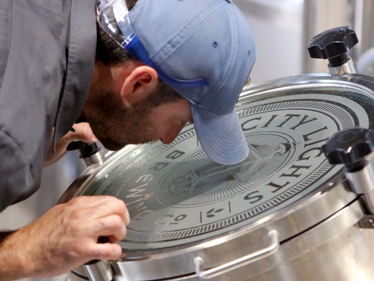 Brewmaster Jimmy Gohsman checks the activity inside