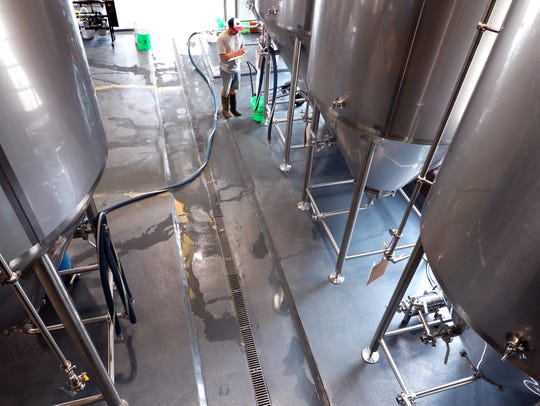 One of the brewers works on a fermentation tanks at