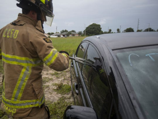 A member of the Cape Coral Fire Department breaks through