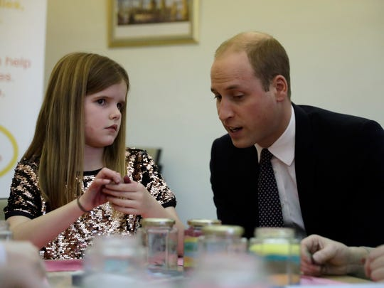 On Jan. 11, 2017, Prince William talks with a girl at the Child Bereavement UK center, where he's a patron.