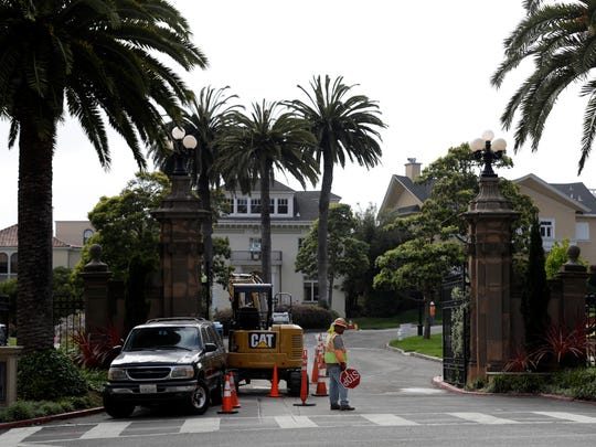 A construction workers stands in front of a gate leading into the Presidio Terrace neighborhood Monday, Aug. 7, 2017, in San Francisco.
