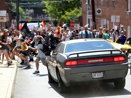 A vehicle drives into a group of protesters demonstrating against a white nationalist rally in Charlottesville, Va., Saturday, Aug. 12, 2017. The nationalists were holding the rally to protest plans by the city of Charlottesville to remove a statue of Confederate Gen. Robert E. Lee. There were several hundred protesters marching in a long line when the car drove into a group of them.