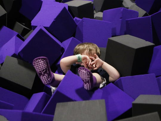 Two-year-old Liam Cantwell covers his eyes as he lies among foam blocks in a pit at Altitude Trampoline Park in Monroe, La. on Thursday, March 31, 2016.