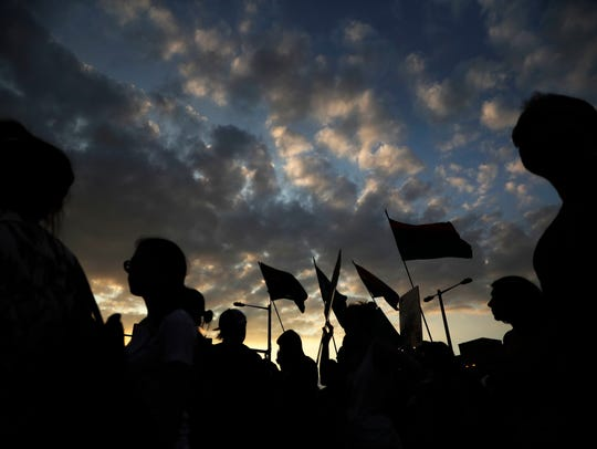 Protesters, silhouetted against the evening sky demonstrate