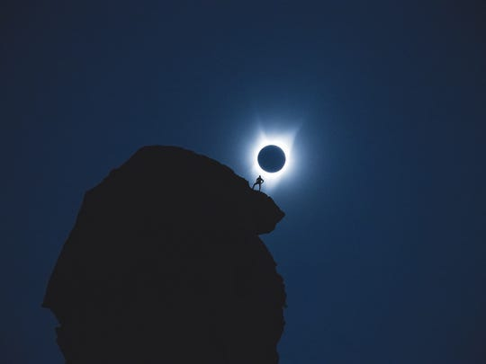 A wider version of the photo Andrew Studer took of a climber at Smith Rock State park during Monday's eclipse