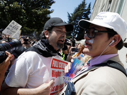 Trump supporter Jovi Val, right, is confronted by an