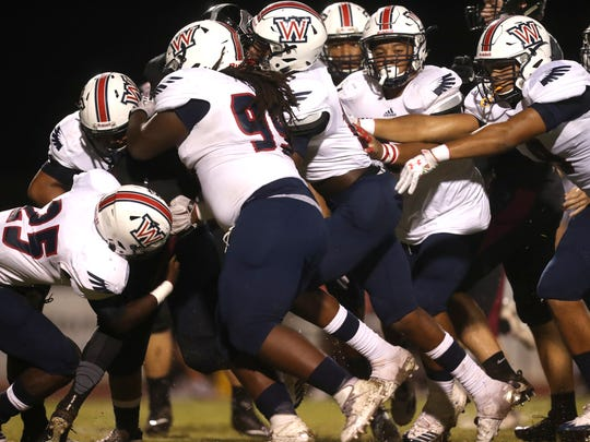 Wakulla gang tackles, with Jazonte Hicks (25) and Isaiah Lewis (99) up front against Chiles' Garrett Greene during their game at Chiles High School on Thursday, Aug. 31, 2017.