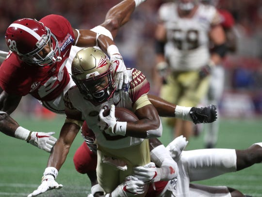 FSU's Nyqwan Murray is tackled by Alabama's Anthony
