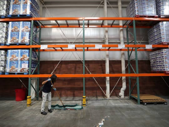 A Costco worker sweeps under the empty shelves where the store usually holds its selection of bottled water, which sold out early last year before Hurricane Irma.