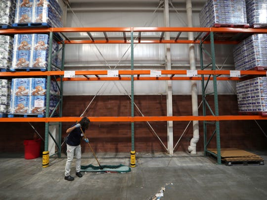 A Costco worker sweeps under the empty shelves where the store usually holds its selection of bottled water, which sold out before noon on Tuesday. Costco representatives said they would have more supplies shipped to the store in the coming days before Hurricane Irma hits the state of Florida.