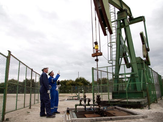 Thierry Oger, right, a production manager for Canadian based Vermilion oil company, and Jean-Pascal Simart, head of public affairs, watch an oil rig, Wednesday, Sept. 6, 2017, in Andrezel, south east of Paris . France's government has unveiled a law to ban all production and exploration of oil and natural gas by 2040 on the country's mainland and overseas territories. The move is largely symbolic, however, as France's oil and gas production represents just 1 percent of national consumption - the rest is imported.